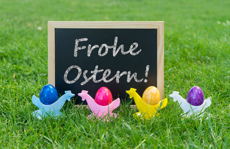 Easter card with chalkboard and colorful easter eggs with german text: Happy Easter