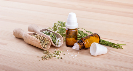 Homeopathic remedy with flowering yarrow and two spoons with a wooden background