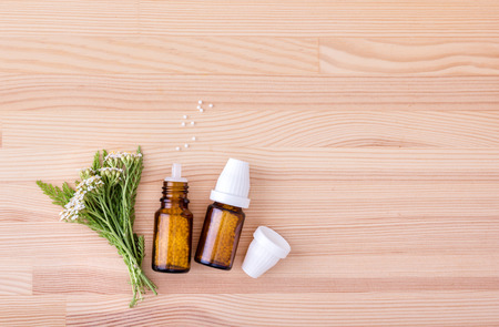 Top view of Homeopathic remedy with flowering yarrow with a wooden background