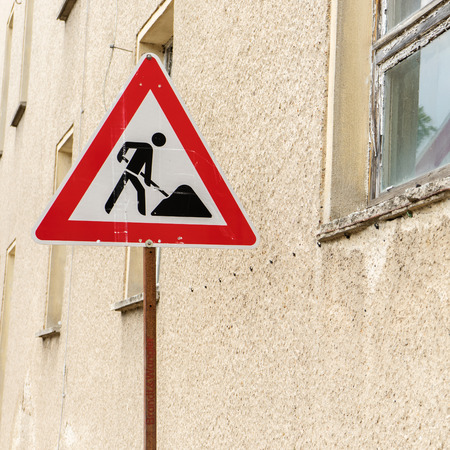 Construction site sign in front of a house wall with windows Standard-Bild