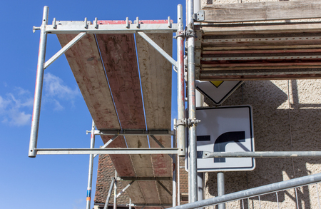 Detail of a scaffolding with street sign in front of a blue sky Standard-Bild