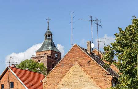 Roofs with TV antennas and church tower in the background Standard-Bild