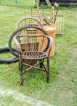 Wicker chair, garden tools and bicycle tires on a flea market Standard-Bild