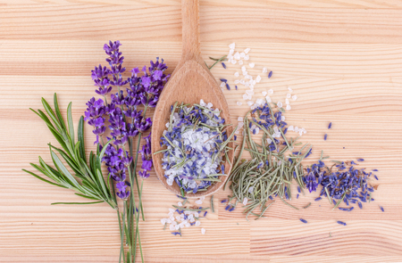 top view of a spoon of rosemary and lavender flowers on a wooden background Standard-Bild