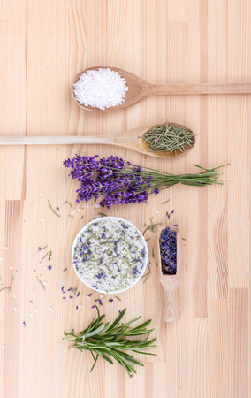 Top view of seasoned salt with rosemary and lavender blossoms on a wooden background