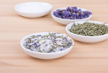 Herbal salt with rosemary and lavender blossoms on a wooden background Standard-Bild