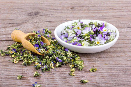 white bowl and wooden spoon with fresh and dried flowers from field pansy Standard-Bild