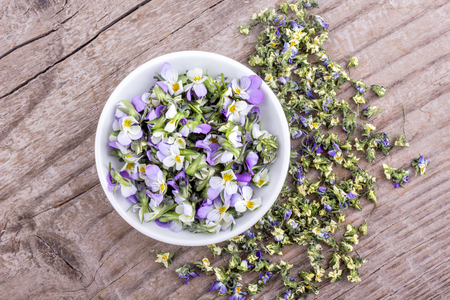 Top view of a white bowl of fresh and dried flowers from field pansy