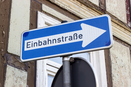 Road sign with german text: one-way street in front of a half-timbered house
