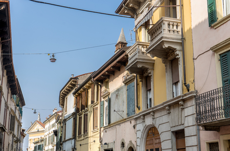Street with pretty, beautiful houses in Verona with balconies and blue sky