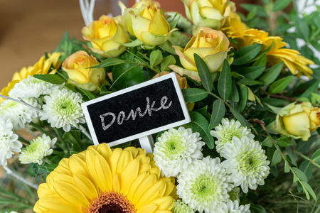 Bouquet of yellow and white roses, gerberas, chrysanthemums and small chalkboard with english text: Thank you