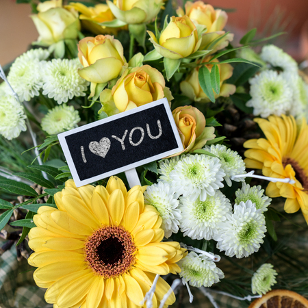Bouquet of yellow and white roses, gerberas, chrysanthemums and a chalkboard with text: I love you Standard-Bild