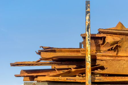 Old, rusty metal parts of wave mugs against a blue sky Standard-Bild