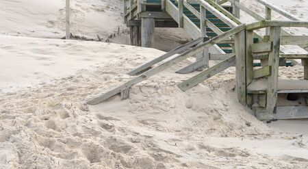 Wooden stairs on the beach are blown with sand Standard-Bild