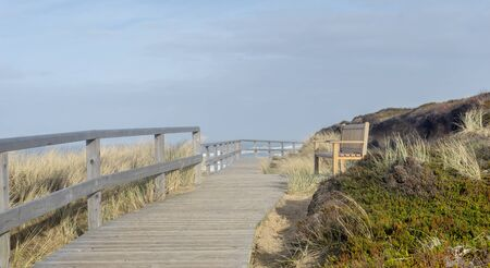 Seascape of the island of Sylt with bench on a dune off the North Sea coast