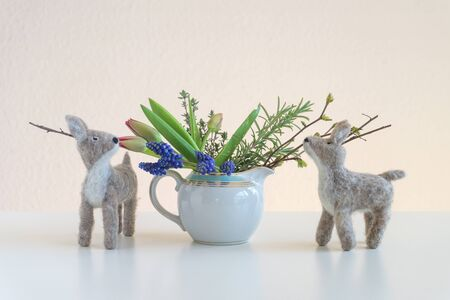 Two felt deers smell on branches and tulips