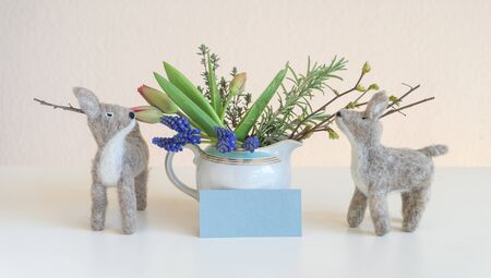 Two felt deers smell on a bouquet of flowers