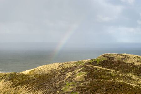 View of the North Sea with rainbow and dunes