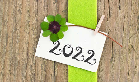 New year card for the Year 2022 with Leafed clover on wooden background