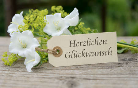 Greeting card with white bell flowers and german text congratulations
