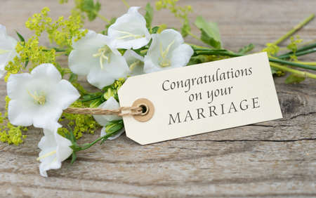 Greeting card with white bell flowers and english text congratulations on your marriage Standard-Bild