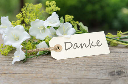 Greeting card with white bell flowers and german text thanks