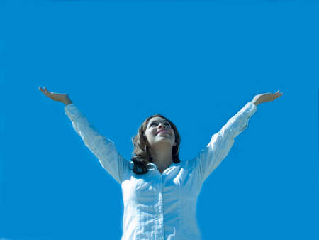 A hispanic woman with arms extended to the sky. Stock Photo