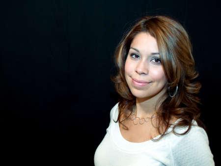Hispanic woman smiling on black