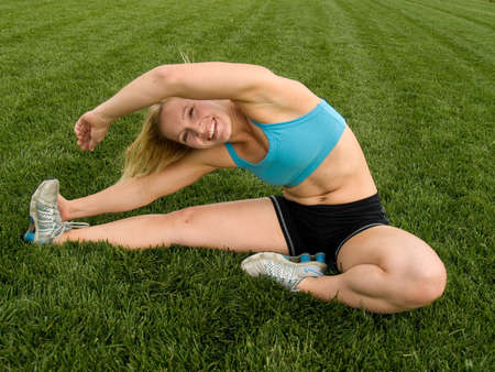 Woman in workout clothing stretching on the grass
