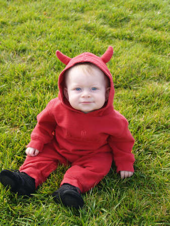 Baby in a devil halloween costume.