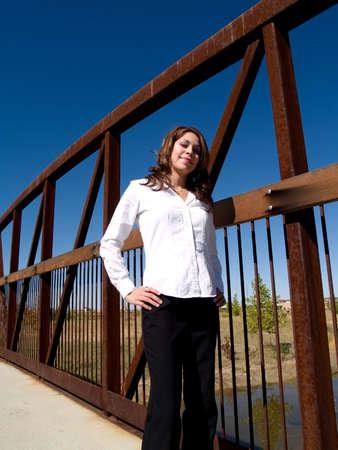 A pretty hispanic girl on a bridge. photo