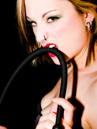 Woman with a riding crop making a come hither gesture. Stock Photo