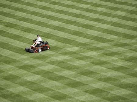 gras maaien: Workman duiten een honkbal veld voor het seizoen. Stockfoto