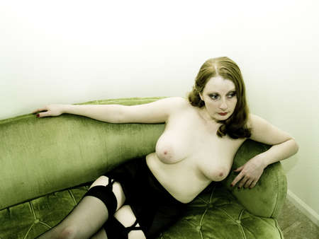 A topless woman lounges on a bright green couch. Stock Photo - 901986