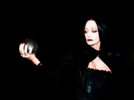 soothsayer: Bola de cristal, celebrada en manos de una fortuna escrutador.  Foto de archivo