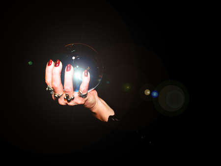 A crystal ball is held in the hands of a fortune teller. Stock Photo
