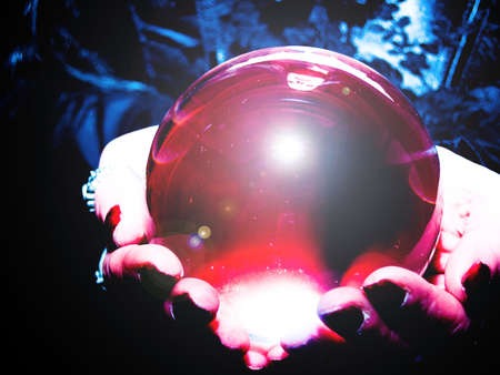 crystal ball glowing in hands Stock Photo