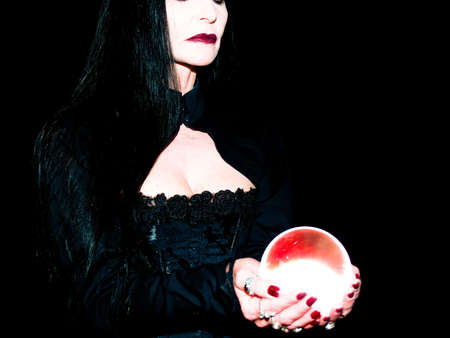 A crystal ball is held in the hands of a fortune teller. photo