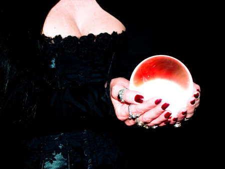 scrying: Crystal ball held in the hands of a fortune teller. Stock Photo