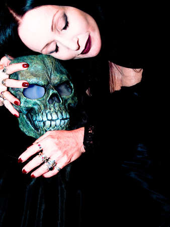 A spooky looking lady rests her head on a halloween skull. photo