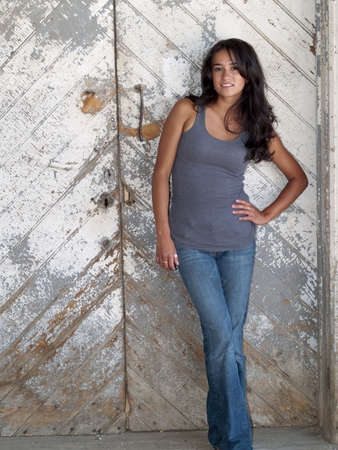 Young, native american woman standing in front of a barn door Stock Photo