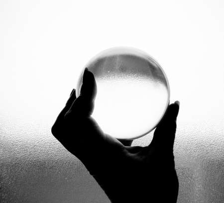 Crystal ball being held in hand in black and white photo