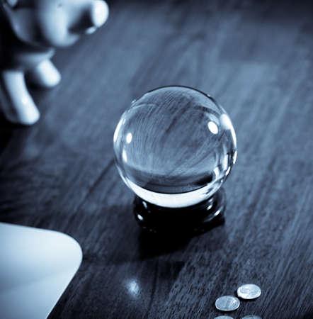 destin: Concept : Financi�re jeu de devinettes avec tirelire, boule de cristal et pi�ces de monnaie dans les tons froids.