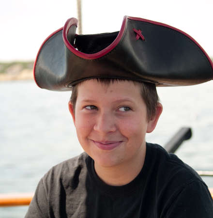 Pre-teen kid in a pirate hat on a boat