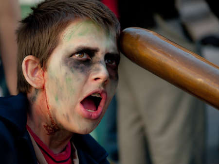 zombie kid getting hit with a baseball bat.