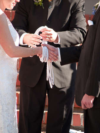 Ancient pagan traditional wedding element.  Hand Fasting or Tying the Knot.  Officiants hands are in slight motion