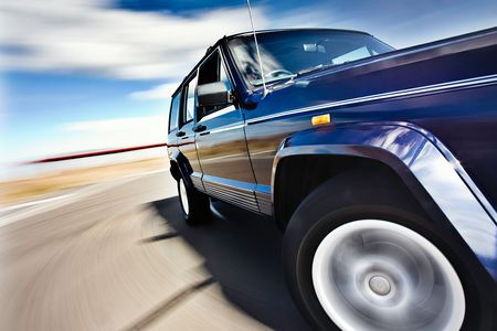 motor vehicle: Blue Car in motion with deep blue sky Stock Photo