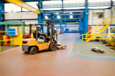 forklift: Forklift driving through  Industrial Factory