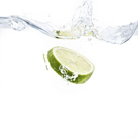 limes: lime slice splashing into water with white background Stock Photo