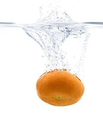Fresh Tangerine splashing into water with white background photo